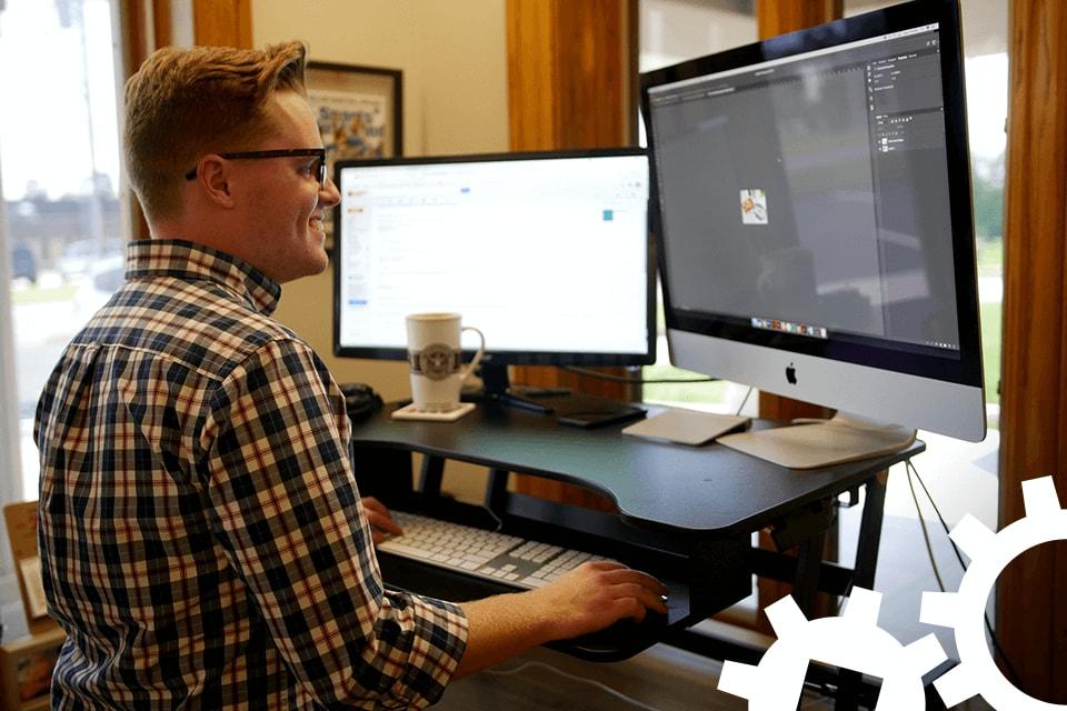 Jimi Adams standing at his desk at Ramsey MediaWorks.