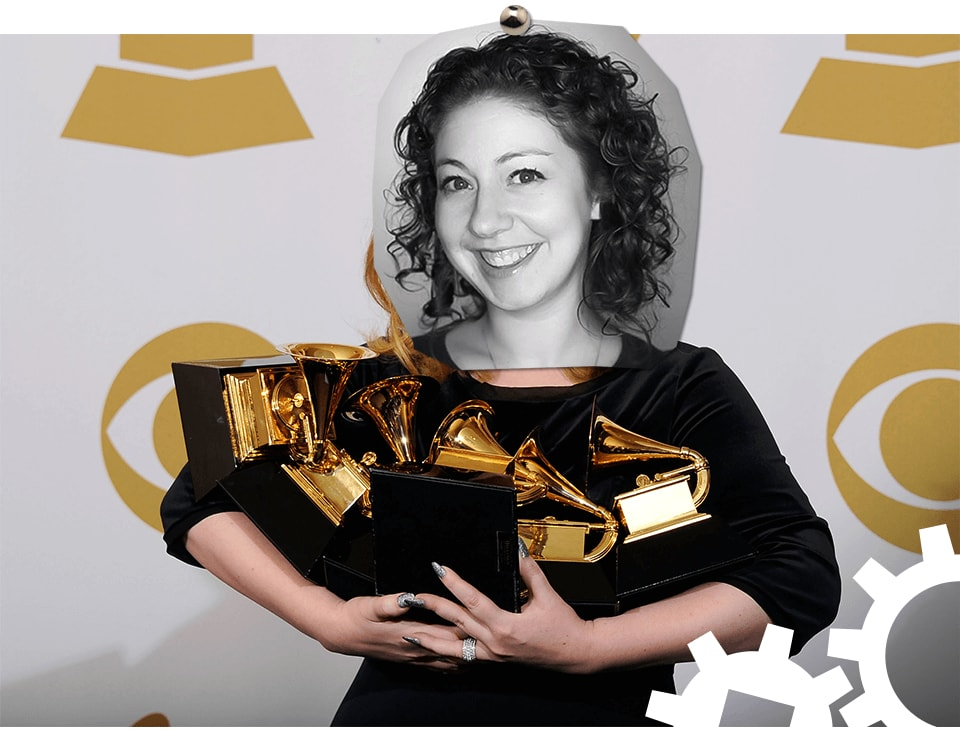Penney's face photoshopped onto someone holding lots of Grammy awards.