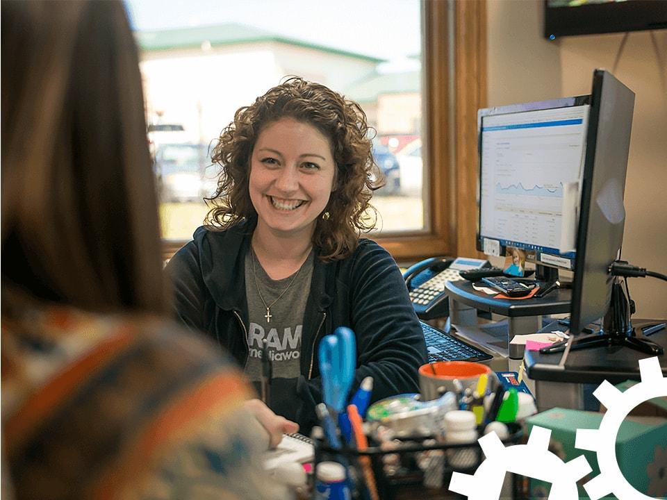 Penney smiling at her desk.
