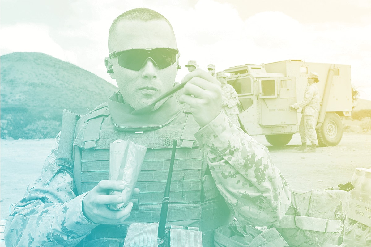 A soldier eating in uniform.