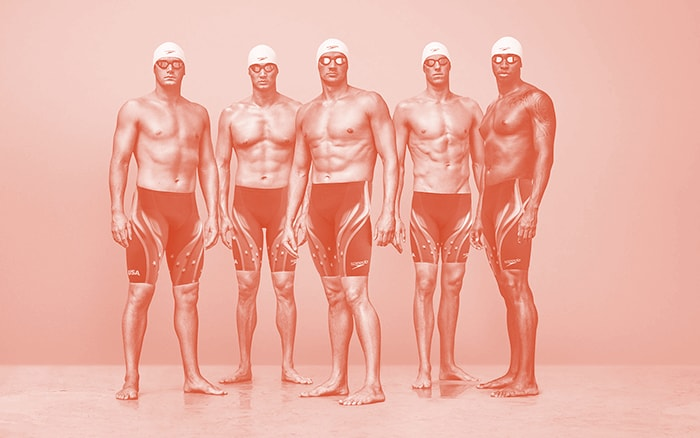 Olympic swimmers wearing caps, goggles, and swimsuits.
